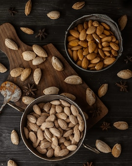 Pistachios and almonds inside black bowles and on a wooden board.