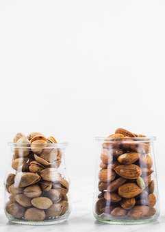 Barattolo di pistacchi e mandorle su superficie di marmo
