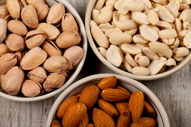 Pistachios, almonds, peanuts in ceramic plates. on the wooden table.