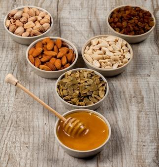 Pistachios, almonds, peanuts, pumpkin seeds, raisins and honey in ceramic plates.