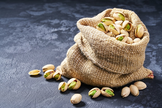 Pistachios in bag on black table. heap or stack of pistachios.
