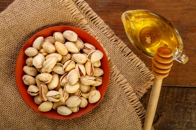 Pistachios in a clay bowl on a sacking next to honey with a spoon on a wooden table.