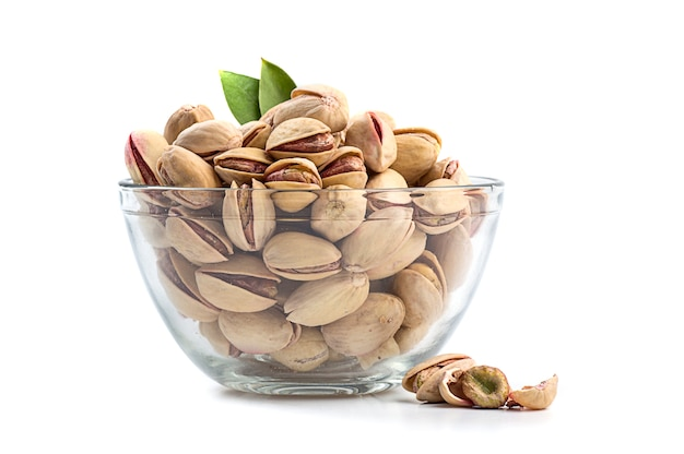 Pistachios in glass bowl on white background
