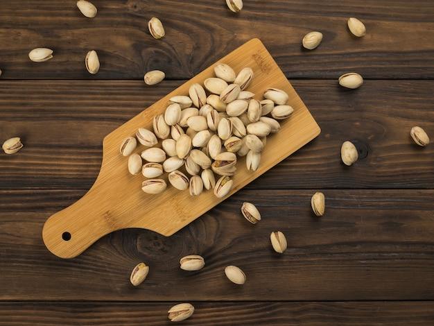 木製のテーブルのまな板の上のピスタチオ。タンパク質と炭水化物の天然源。