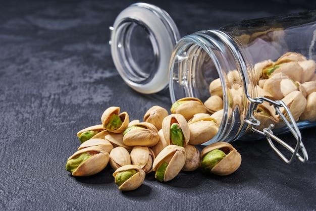 Pistachios in an open glass jar on black table, close-up.