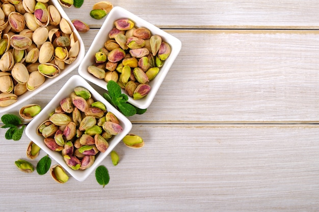 Pistachios on white wooden background