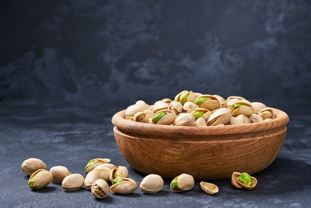Pistachios in wooden bowl on black , close-up.