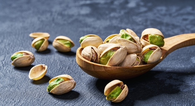Pistachios in wooden spoon on black table, close-up.