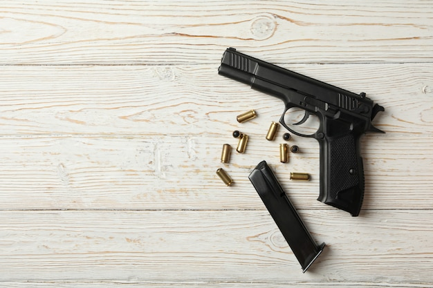 Пистолет, пули и магазин на деревянном