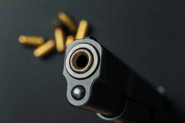 Pistol and bullets on black. self defense weapon