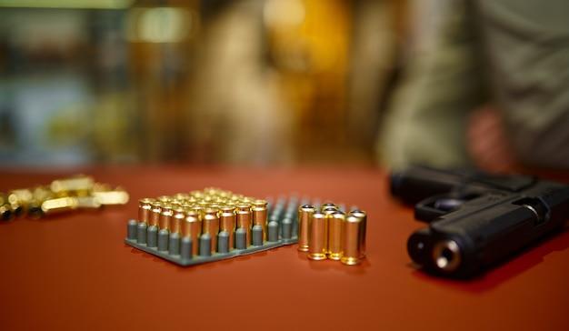 銃店のカウンターに立っているピストルの弾丸