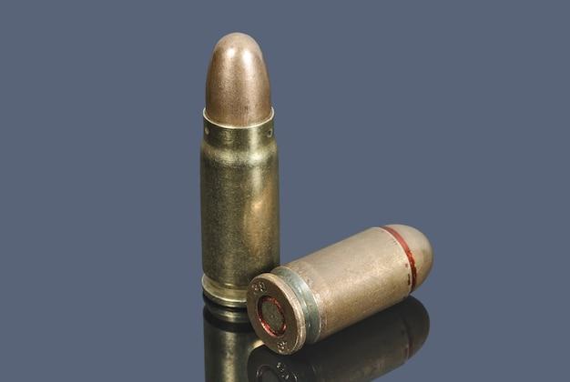 회색 테이블에 구경 7.62mm 및 9mm의 권총 카트리지