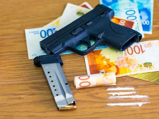 권총 총, 이스라엘 새 셰켈 지폐 배경에 총알. 마피아와 범죄 생활. 나무 테이블에 사용할 준비가 된 코카인. 코카인 마약 중독 개념입니다. 백색 분말