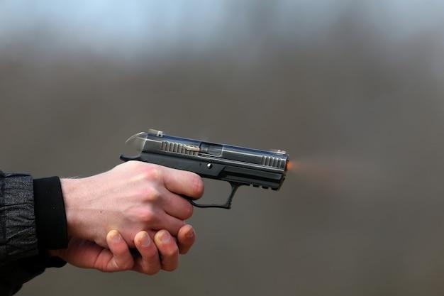 두 손으로 총을 쏘는 권총, 셔터에서 나오는 포탄과 푸른 연기.