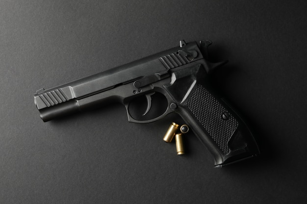 Pistol and traumatic bullets on black. self defense weapon