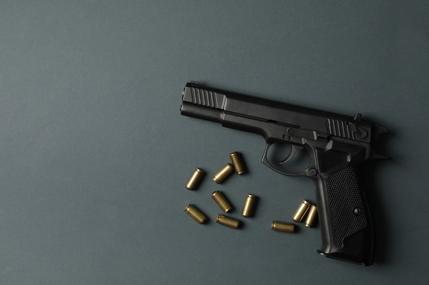 Pistol and traumatic bullets on dark gray. self defense weapon