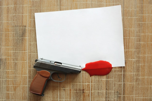 Pistol, white sheet of paper and scarlet blood on wooden board.