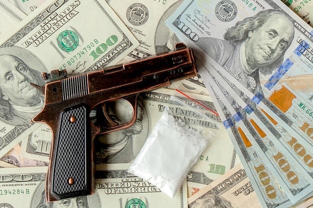 달러의 배경에 권총과 마약.