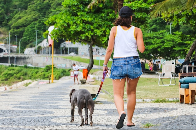 Собака питбуль гуляет по пляжу с бразильской девушкой. солнечный день. выборочный фокус.
