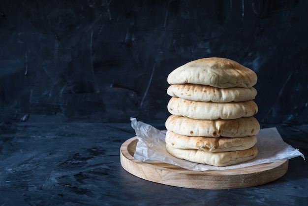 Pita bread on black wooden background with copy space