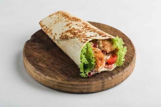 흰색 나무 보드에 닭고기와 신선한 야채와 함께 피타 빵 롤