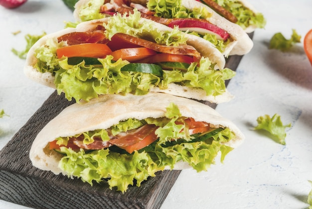 Pita bread sandwich with fresh vegetables on a light concrete table
