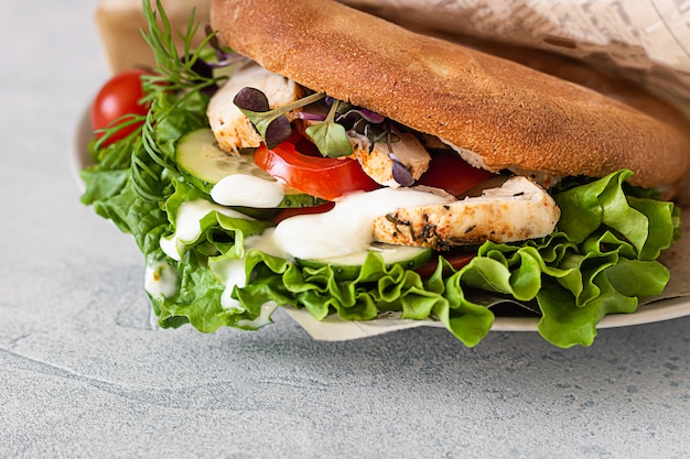 Pita bread sandwich with fresh vegetables and roasted chicken