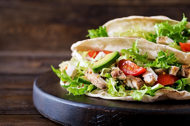 Pita bread sandwiches with grilled chicken meat, avocado, tomato, cucumber and lettuce served on wooden table