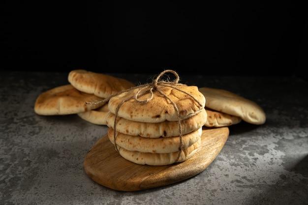 Пита, мягкие лепешки, перевязанные шпагатом на деревенской деревянной доске на темном фоне