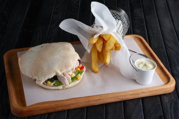Pita bread with chicken and vegetables served with fried potato