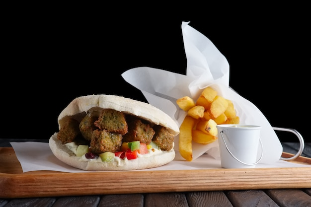 Pita bread with falafel, vegetables and fried potatos on wooden plate