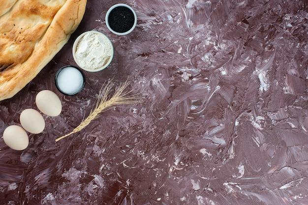 Focaccia pita con uova di gallina e farina su sfondo chiaro.