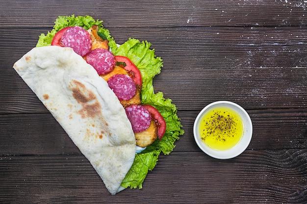 Лавочка, питта хлеб с колбасой, жареная курица, салат, помидоры, соус, майонез. оливковое масло с зеленью и специями на темном, сером или коричневом деревянном столе. быстрая уличная нездоровая нездоровая пища