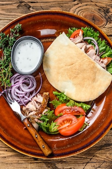 Pita salad with roasted chicken and vegetables on a plate.