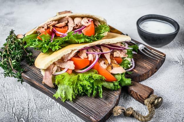 ローストチキン、野菜、おいしいソースのピタサンドイッチ