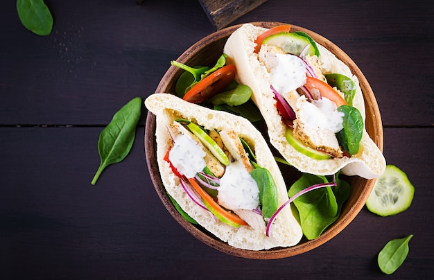 Pita stuffed with chicken, tomato, cucumber and spinach on wooden surface