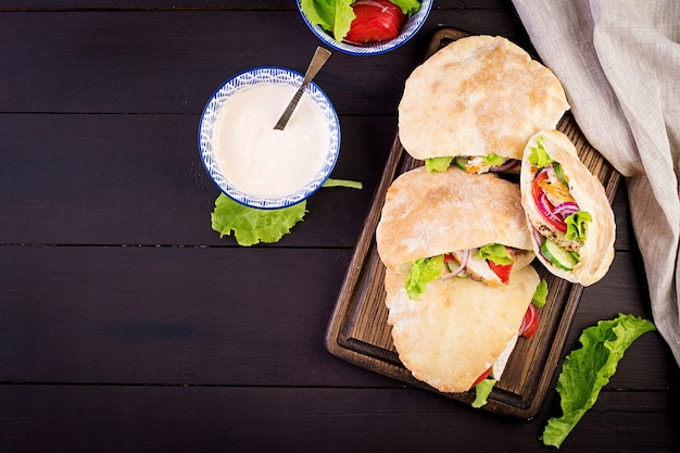 Pita stuffed with chicken, tomato and lettuce on wooden, middle eastern cuisine, top view