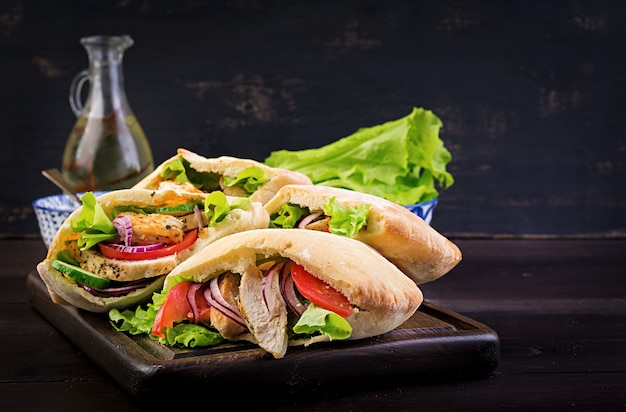 Pita stuffed with chicken, tomato and lettuce on wooden, middle eastern cuisine.