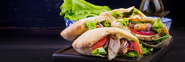 Pita stuffed with chicken, tomato and lettuce on wooden table. middle eastern cuisine.