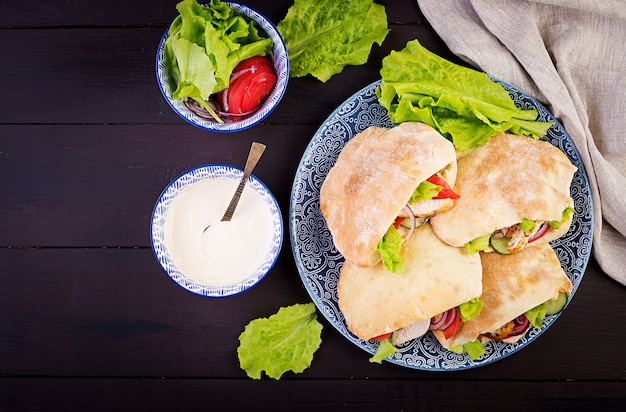 Pita stuffed with chicken, tomato and lettuce, and yoghurt sauce