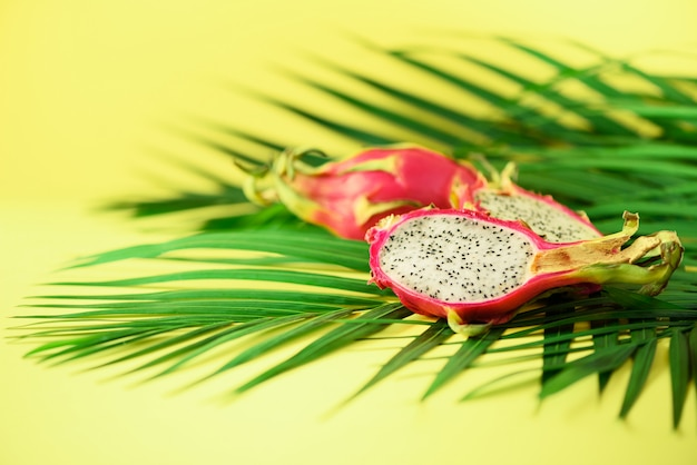 Pitahaya or dragon fruit over tropical green palm leaves on yellow background. pop art design, creative summer concept.