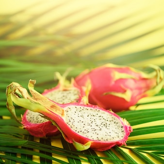 Pitahaya or dragon fruit over tropical green palm leaves on yellow background. top view with copy space. pop art design, creative summer concept.