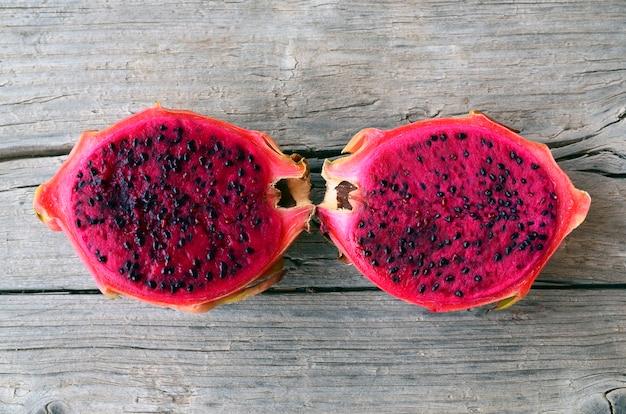 Экзотические спелые розовые плоды питайи или дракона. красный тропический плодоовощ pitahaya отрезал в половине на старом деревянном столе. селективный фокус.