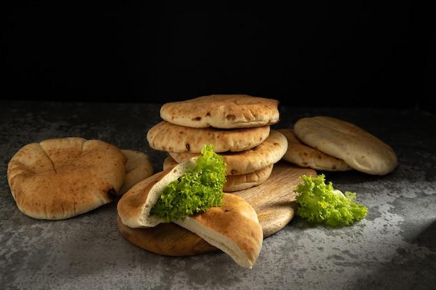 Мягкие пирожные питас на деревянной доске на темном фоне