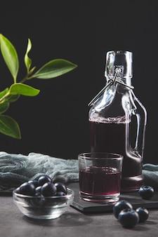 Кувшин и стакан с соком черники на темном фоне.