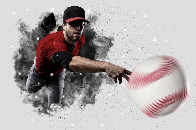 煙の爆発から出てくる赤い制服を着た投手野球選手。