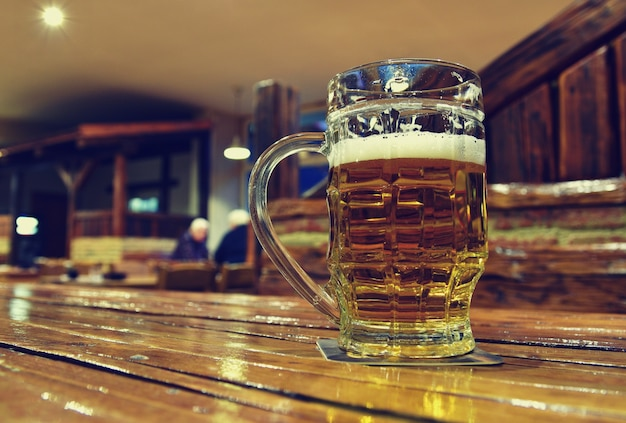 Pitcher of beer on wooden table