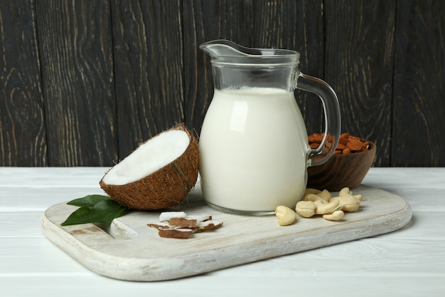 白い木製のテーブルにミルク、ココナッツ、ナッツのピッチャー