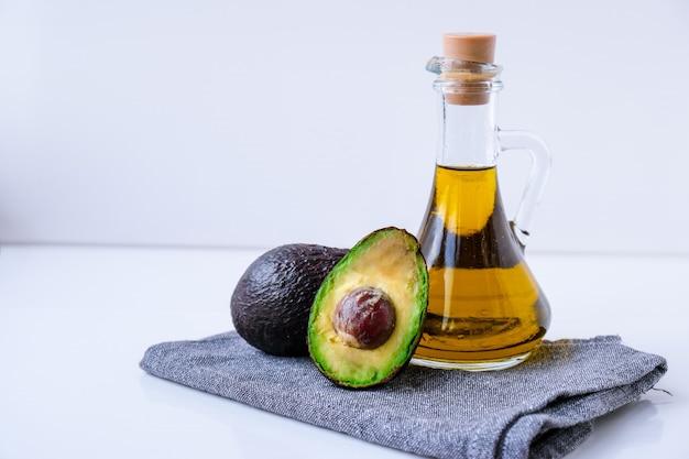 천연 오일과 신선하게 익은 하스 아보카도의 투수. 부엌에서 음식을 준비합니다. 재료. 건강 식품의 개념입니다. 건강한 식생활. 케토 다이어트