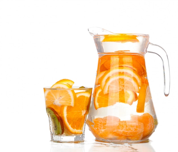 Pitcher with a refreshing drink with lemon slices of orange and kiwi on white background